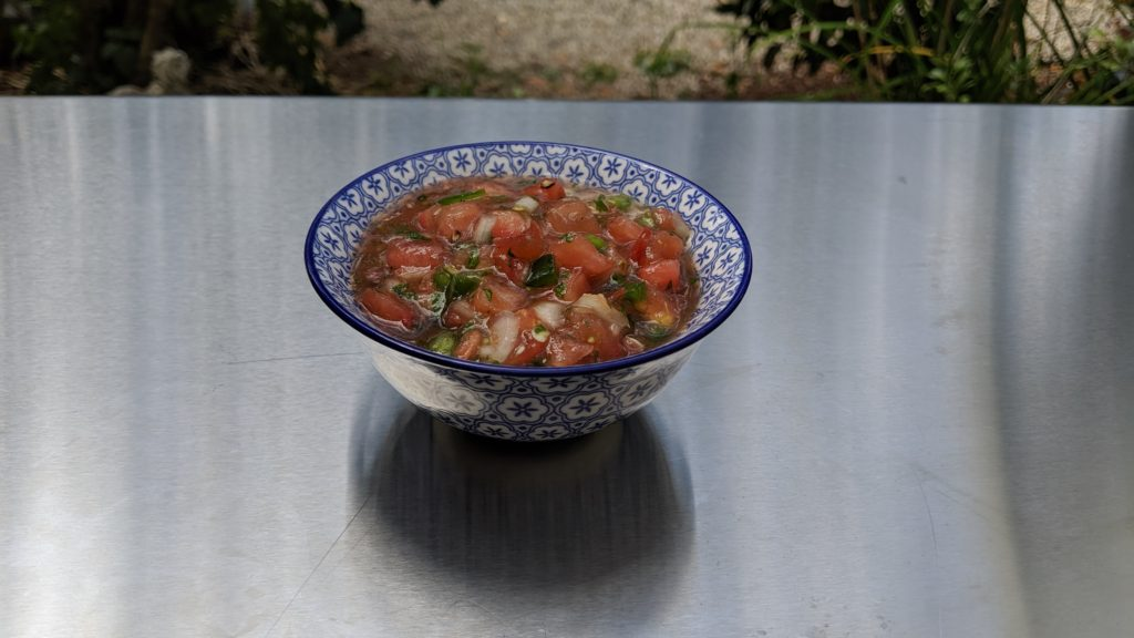 Purple Cherokee Salsa in a blue and white bowl on a stainless steel countertop.