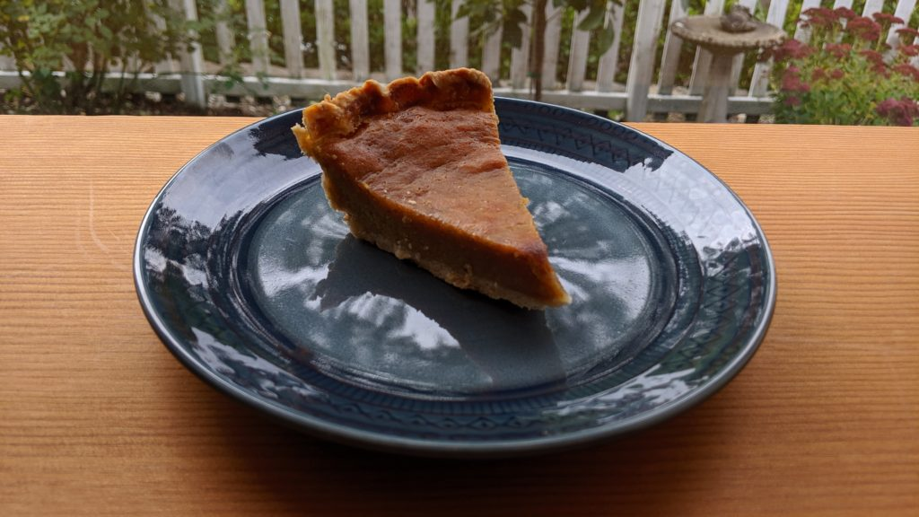 A slice of fresh pumpkin pie on a navy blue plate on a vertical-grain Douglas Fir table with a view of a white picket fence out the window.