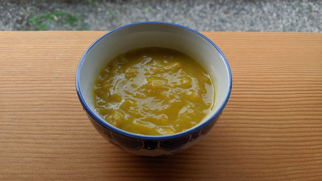 A small bowl of pumpkin soup on a wood table.