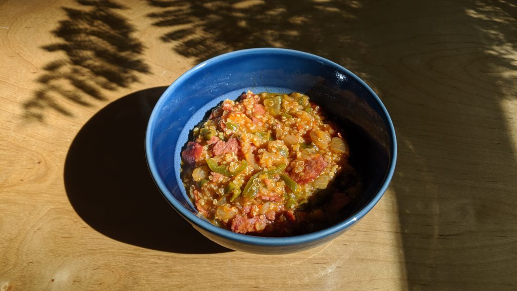 Jalapeno Quinoa Sausage Stew in a blue bowl on a sunlit wooden table with the shadow of Jacaranda tree leaves.