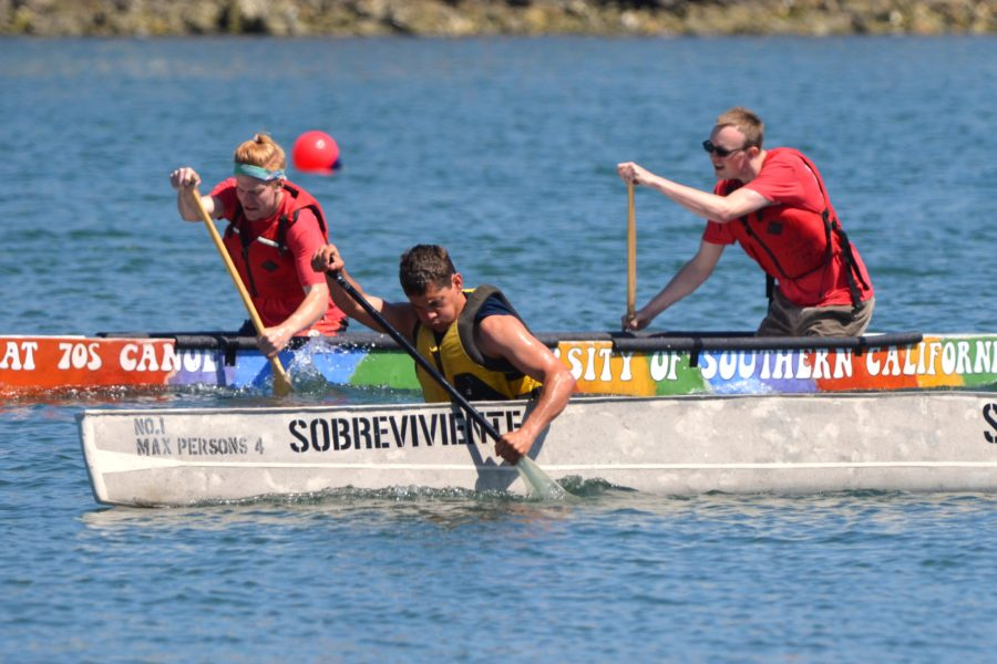 Two concrete canoes with three paddlers racing them in the water
