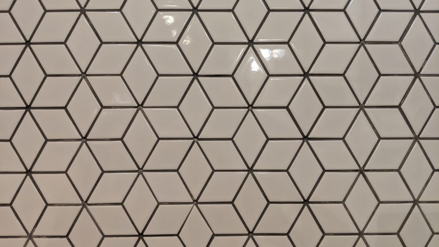 Glossy white porcelain tile with gray grout in a rhombus pattern